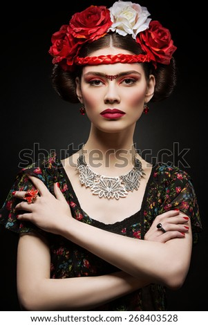 Beautiful young woman with bright red make up looking like Frida Kahlo. Over black background - stock photo