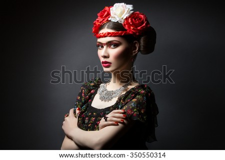 Beautiful young woman with bright red make up looking like Frida Kahlo. Over black background. Copy space. - stock photo