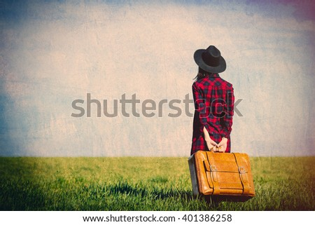 beautiful young woman with brown suitcase in the field - stock photo