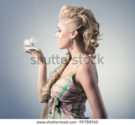 Beautiful young woman with butterfly - stock photo