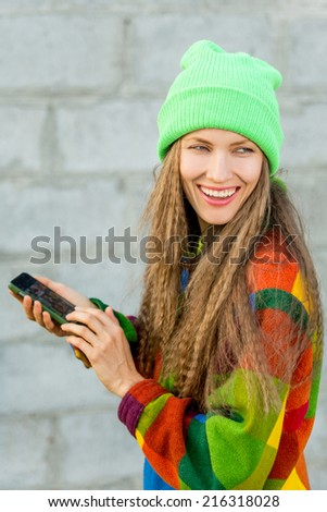 Beautiful young woman with cell phone. Cute smiling young caucasian teenage girl using smart phone outdoors over grunge grey background - stock photo
