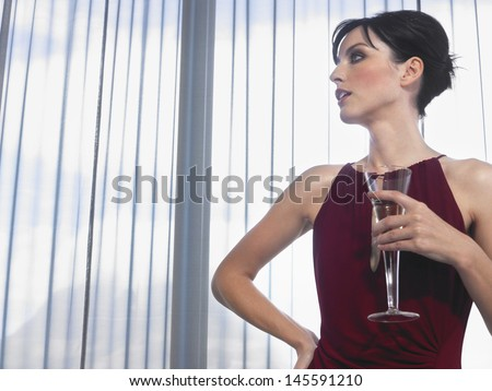 Beautiful young woman with champagne glass in front of curtains - stock photo