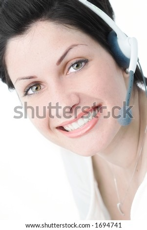 Beautiful young woman with charming big green eyes is receiving calls on a headset. - stock photo