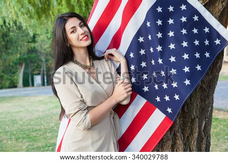 Beautiful young woman with classic dress near american flag in the park. fashion model holding us smiling and looking at camera. usa lifestyle. business style clothing lady posing and toothy smile.