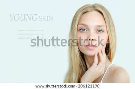 Beautiful young woman with clean fresh skin and natural make up on light background - stock photo