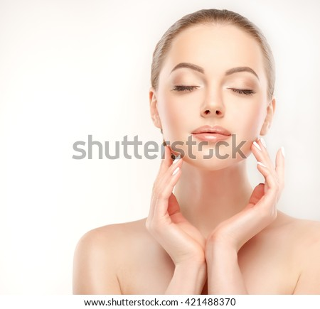 Beautiful Young Woman with Clean Fresh Skin  touch her face . Facial  treatment   . Cosmetology , beauty  and spa .   - stock photo
