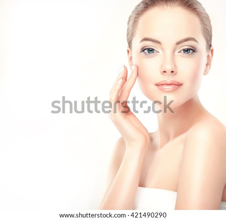 Beautiful Young Woman with Clean Fresh Skin  touch own face . Facial  treatment   . Cosmetology , beauty  and spa .  - stock photo