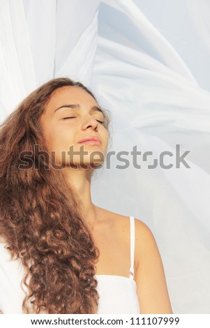 Beautiful young woman with closed eyes on white fabric background