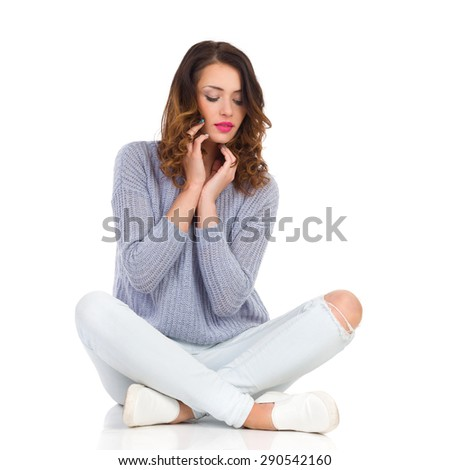 Beautiful young woman with closed eyes sitting on a floor with legs crossed, holding hands on chin. Full length studio shot isolated on white. - stock photo