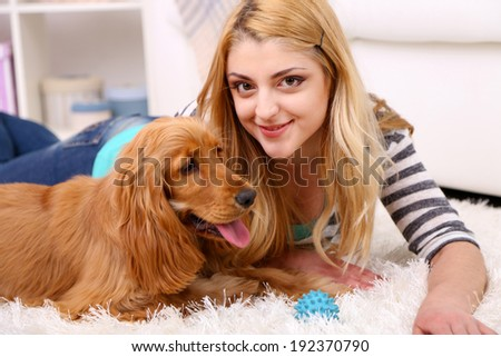 Beautiful young woman with cocker spaniel in room