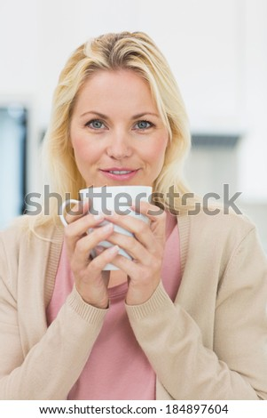 Beautiful young woman with coffee cup in the kitchen at home - stock photo
