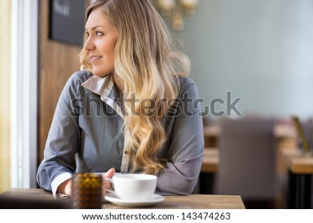 Beautiful young woman with coffee cup looking away at coffeeshop