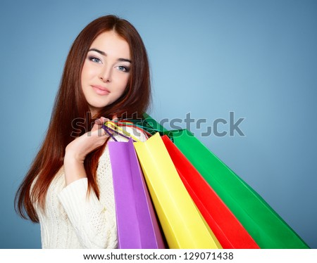 beautiful young woman with colored shopping bags over blue background - stock photo