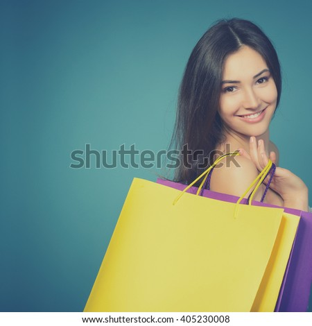 beautiful young woman with colored shopping bags over blue background. Best therapy is shopping.