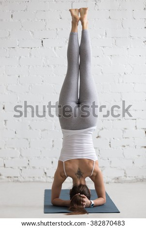 Beautiful young woman with cool flower tattoo on her back working out indoors, doing yoga exercise on blue mat, supported headstand, salamba sirsasana, rear view, full length