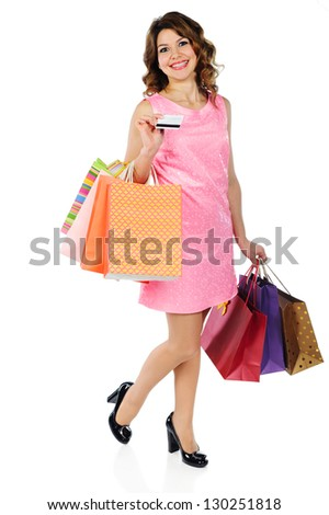 Beautiful young woman with credit card and shopping bags isolated on white background