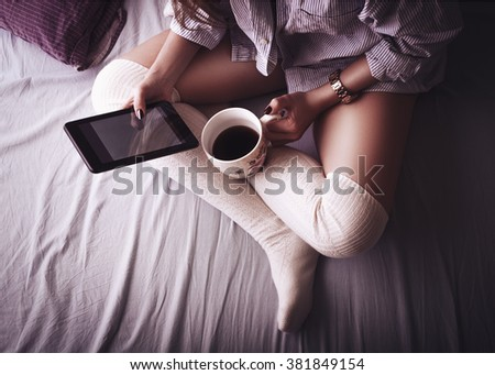 Beautiful young woman with crossed legs drinking coffe and surfing internet and social media news on tablet computer in her morning bed
