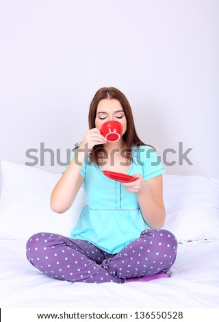 Beautiful young woman with cup of coffee in bed - stock photo