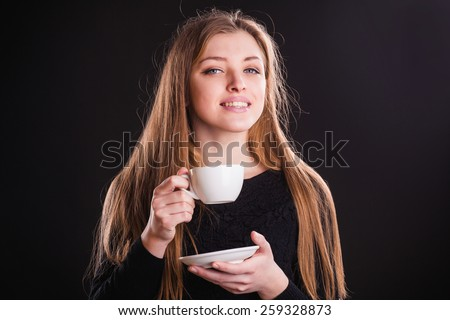 Beautiful young woman with cup of coffee, on black background