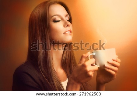 Beautiful young woman with cup of coffee on brown background - stock photo