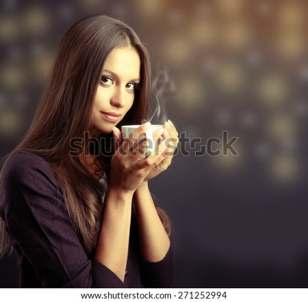 Beautiful young woman with cup of coffee on dark background - stock photo