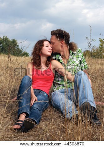 Beautiful young woman with curly hair and man sit in the field. The young man is kissing the lady on her cheek. - stock photo