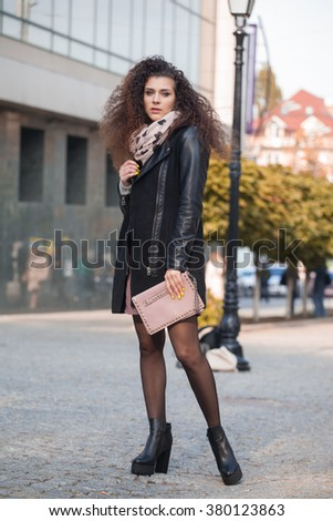Beautiful young woman with curly hair walking in the city