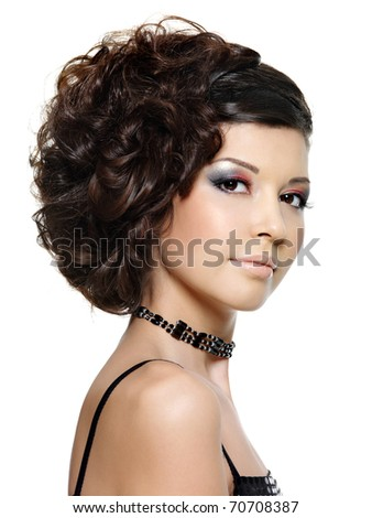 Beautiful young woman with curly hairstyle and bright makeup - on white background