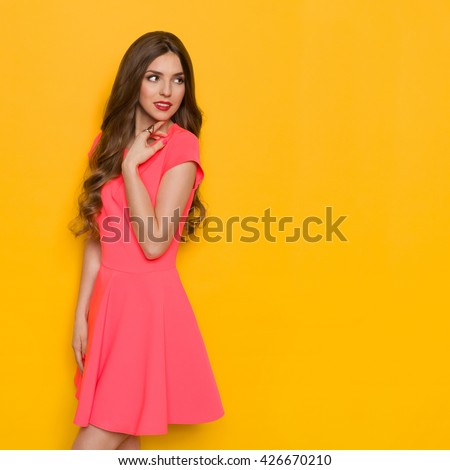 Beautiful young woman with curly long brown hair in pink mini dress looking over her shoulder and holding hand on chin. Three quarter length studio shot on yellow background. - stock photo