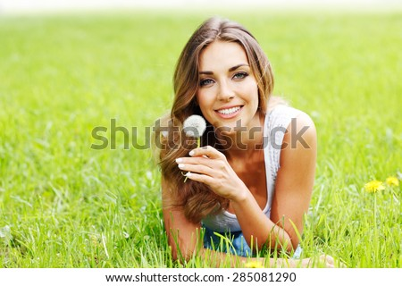 beautiful young woman with dandelion lying on grass