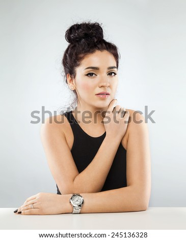Beautiful young woman with dark curly hair and perfect skin, with a watch at hand. on a white  background - stock photo