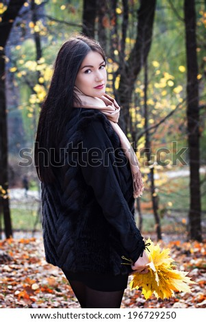 beautiful young woman with dark hair in autumn park