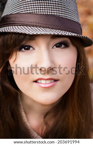 beautiful young woman with dark hair in autumn park. portrait