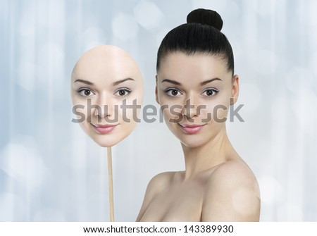 Beautiful young woman with dark skin and light skin face mask-skin whitening concept - stock photo