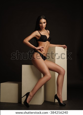 Beautiful young woman with dark straight hair, almond-shaped eyes and bronzed skin is sitting and posing in the black basic underwear collection in the studio on the dark brown background - stock photo