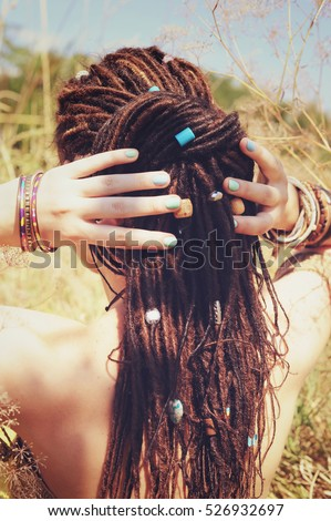 Beautiful young woman with dreadlocks hairstyle gathered in a ponytail, decorated assorted beads, sunny outdoor, no face