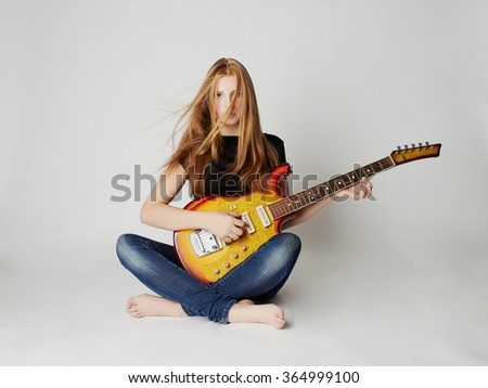 beautiful young woman with electric guitar.sexy girl in jeans.rock music - stock photo