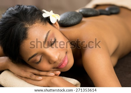 Beautiful young woman with eyes closed receiving hot stone massage at salon spa - stock photo