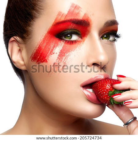 Beautiful young woman with fantasy makeup eating strawberry. Beauty and makeup concept. High fashion beauty portrait isolated on white. Colorful face - stock photo