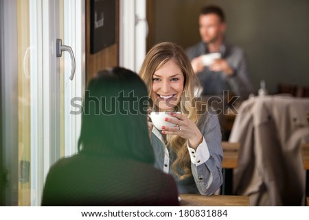 Beautiful young woman with female friend having coffee at cafe - stock photo