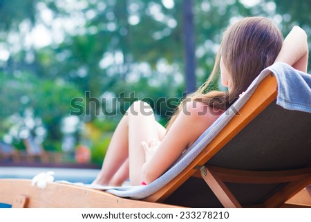 Beautiful young woman with flower in hair relaxing on sun lounger near pool - stock photo