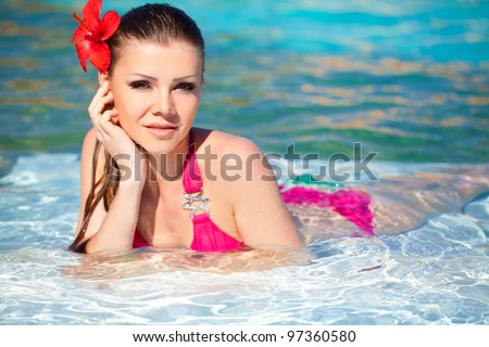 Beautiful young woman with flower resting in the pool of expensive hotel - stock photo