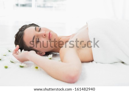 Beautiful young woman with flowers lying in beauty salon