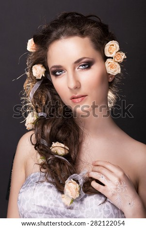 Beautiful young woman with  flowers on her long hair - stock photo