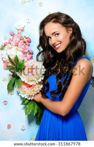Beautiful young woman with flowers smiling at camera. Beauty, fashion. Healthcare, spa. Natural cosmetics and teeth care. - stock photo