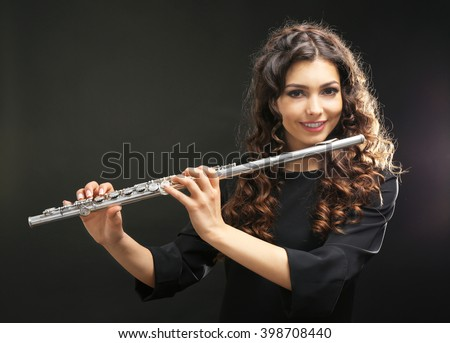 Beautiful young woman with flute on black background