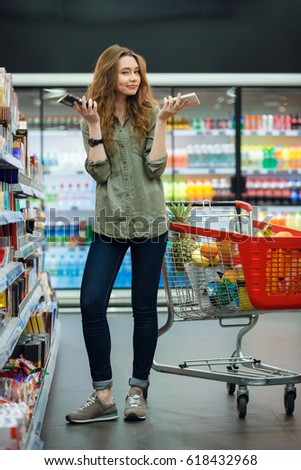 Beautiful young woman with food trolley shopping in supermarket and deciding what to buy