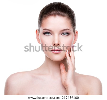 Beautiful young woman with fresh clean skin that touches her face with a hand -  isolated on white. - stock photo
