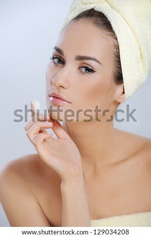 Beautiful young woman with fresh health skin applying cosmetics cream on the face - stock photo