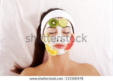 Beautiful young woman with fruit mask on a face - stock photo